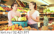 Купить «Positive family couple standing with full cart after shopping and pointing to shelves in fruit store», видеоролик № 32421971, снято 26 мая 2019 г. (c) Яков Филимонов / Фотобанк Лори