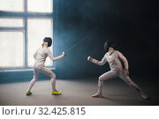 Купить «A fencing training in the studio - two women in white protective costumes having a duel», фото № 32425815, снято 4 ноября 2019 г. (c) Константин Шишкин / Фотобанк Лори