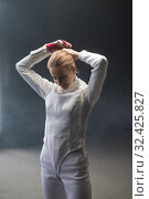 Купить «A young woman fencer putting her hair up into a bun before the training», фото № 32425827, снято 4 ноября 2019 г. (c) Константин Шишкин / Фотобанк Лори