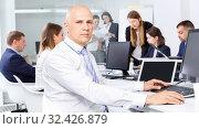 Купить «Confident businessman concentrated on work with laptop in coworking space», фото № 32426879, снято 21 апреля 2018 г. (c) Яков Филимонов / Фотобанк Лори