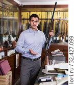 Salesman in hunting shop demonstrating shotgun. Стоковое фото, фотограф Яков Филимонов / Фотобанк Лори