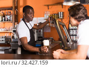 Купить «Young man bartender giving beer with foam to man client», фото № 32427159, снято 28 августа 2019 г. (c) Яков Филимонов / Фотобанк Лори