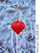 Купить «Christmas red glass heart-shaped ball on branches of tree.», фото № 32428335, снято 24 декабря 2017 г. (c) Kira_Yan / Фотобанк Лори
