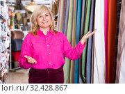 Купить «Positive mature female seller offering curtain in store», фото № 32428867, снято 17 января 2018 г. (c) Яков Филимонов / Фотобанк Лори