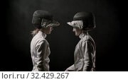 Купить «Fencing training - two young women walking off the dark and greeting each other before the duel», видеоролик № 32429267, снято 1 апреля 2020 г. (c) Константин Шишкин / Фотобанк Лори