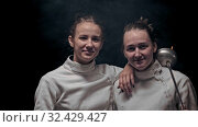 Купить «Two young women fencers standing in the dark studio - looking in the camera», видеоролик № 32429427, снято 1 апреля 2020 г. (c) Константин Шишкин / Фотобанк Лори