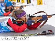 Kamchatka sportswoman biathlete Vakhrusheva Valentina rifle shooting in prone position. Biathlete in shooting range (2019 год). Редакционное фото, фотограф А. А. Пирагис / Фотобанк Лори