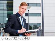 Geschäftsmann schreibt unterwegs mit einem Stift in eine Akte. Стоковое фото, фотограф Zoonar.com/Robert Kneschke / age Fotostock / Фотобанк Лори