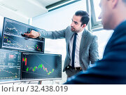 Купить «Businessmen trading stocks online. Stock brokers looking at graphs, indexes and numbers on multiple computer screens. Colleagues in discussion in traders office. Business success concept.», фото № 32438019, снято 9 июля 2020 г. (c) easy Fotostock / Фотобанк Лори