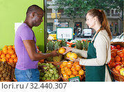 Купить «Seller woman is helping man choose fresh oranges in the fruit market.», фото № 32440307, снято 26 мая 2018 г. (c) Яков Филимонов / Фотобанк Лори