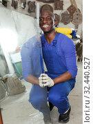 Experienced African American glazier choosing glass for cutting in workshop. Стоковое фото, фотограф Яков Филимонов / Фотобанк Лори