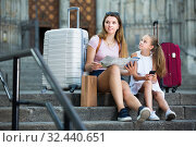 Young female and daughter tourists using map and phone. Стоковое фото, фотограф Яков Филимонов / Фотобанк Лори