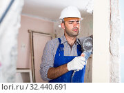 Constructor in helmet is sawing wall with circular saw. Стоковое фото, фотограф Яков Филимонов / Фотобанк Лори
