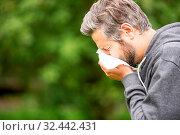Mann mit Allergie und Heuschnupfen beim Niesen in ein Taschentuch. Стоковое фото, фотограф Zoonar.com/Robert Kneschke / age Fotostock / Фотобанк Лори