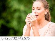 Frau hat Schnupfen und eine Allergie und niest in ein Taschentuch. Стоковое фото, фотограф Zoonar.com/Robert Kneschke / age Fotostock / Фотобанк Лори
