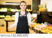 Купить «Smiling girl seller displaying assortment», фото № 32455655, снято 23 ноября 2016 г. (c) Яков Филимонов / Фотобанк Лори