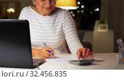 Купить «senior woman filling tax form at home in evening», видеоролик № 32456835, снято 18 ноября 2019 г. (c) Syda Productions / Фотобанк Лори