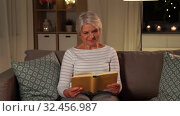 Купить «happy senior woman reading book at home in evening», видеоролик № 32456987, снято 18 ноября 2019 г. (c) Syda Productions / Фотобанк Лори