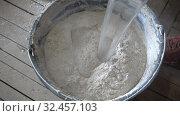 Купить «Builder fills water into dry construction mixture, plaster,Repair and construction,slow motion», видеоролик № 32457103, снято 3 ноября 2009 г. (c) Куликов Константин / Фотобанк Лори