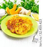 Оладьи из тыквы с сыром в зеленой тарелке на светлой доске. Стоковое фото, фотограф Резеда Костылева / Фотобанк Лори