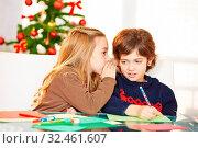 Mädchen flüstert Junge ihren Wunsch ins Ohr zu Weihnachten. Стоковое фото, фотограф Zoonar.com/Robert Kneschke / age Fotostock / Фотобанк Лори