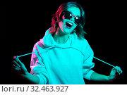 Купить «woman wearing hoodie in neon lights over black», фото № 32463927, снято 30 сентября 2019 г. (c) Syda Productions / Фотобанк Лори