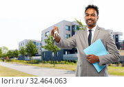 indian man realtor with key and folder in city. Стоковое фото, фотограф Syda Productions / Фотобанк Лори