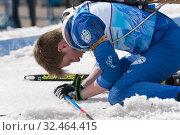 Купить «Sportsman biathlete Danila Smolyakov lies on snow at finish, relaxes after rifle shooting, skiing distance. Regional youth biathlon competitions East Cup», фото № 32464415, снято 13 апреля 2019 г. (c) А. А. Пирагис / Фотобанк Лори
