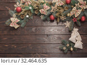 Купить «fir branches with Christmas decor on old dark wooden background», фото № 32464635, снято 14 ноября 2019 г. (c) Майя Крученкова / Фотобанк Лори