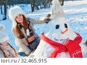 Mutter und Tochter bauen zusammen einen Schneemann im Winter im Garten. Стоковое фото, фотограф Zoonar.com/Robert Kneschke / age Fotostock / Фотобанк Лори