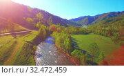 Купить «Mid air flight over fresh mountain river and meadow at sunny summer morning. Rural dirt road below.», видеоролик № 32472459, снято 17 мая 2017 г. (c) Александр Маркин / Фотобанк Лори
