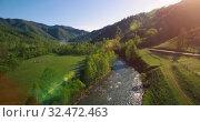 Купить «Mid air flight over fresh mountain river and meadow at sunny summer morning. Rural dirt road below.», видеоролик № 32472463, снято 18 мая 2017 г. (c) Александр Маркин / Фотобанк Лори