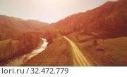 Купить «Mid air flight over fresh mountain river and meadow at sunny summer morning. Rural dirt road below. Cows and car.», видеоролик № 32472779, снято 4 июня 2017 г. (c) Александр Маркин / Фотобанк Лори