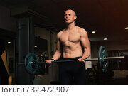 Купить «Muscular bodybuilder guy doing exercises with barbell in gym. Brutal strong athletic man pumping up muscles and train in gym workout.», фото № 32472907, снято 31 октября 2019 г. (c) Иван Карпов / Фотобанк Лори