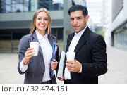 Businessman and his woman colleague in suit are standing with folder and coffee. Стоковое фото, фотограф Яков Филимонов / Фотобанк Лори