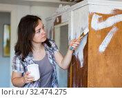Woman makes repairs in the apartment and paints closet. Стоковое фото, фотограф Яков Филимонов / Фотобанк Лори