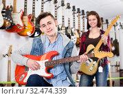 Smiling boy and girl teenagers examining electric guitars. Стоковое фото, фотограф Яков Филимонов / Фотобанк Лори