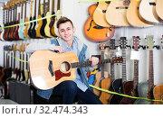 Купить «Teenager choosing acoustic guitars», фото № 32474343, снято 14 февраля 2017 г. (c) Яков Филимонов / Фотобанк Лори