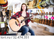 Купить «Charming girl examining various acoustic guitars», фото № 32474351, снято 14 февраля 2017 г. (c) Яков Филимонов / Фотобанк Лори