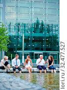 Entspanntes Business Team macht ein Meeting im Sommer mit den Füßen im Teich. Стоковое фото, фотограф Zoonar.com/Robert Kneschke / age Fotostock / Фотобанк Лори