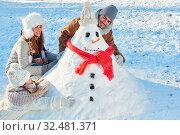 Eltern und Kind bauen einen Schneemann und spielen im Schnee im Winter. Стоковое фото, фотограф Zoonar.com/Robert Kneschke / age Fotostock / Фотобанк Лори