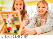 Zwei Mädchen als Schüler in der Grundschule lernen rechnen mit dem Abakus. Стоковое фото, фотограф Zoonar.com/Robert Kneschke / age Fotostock / Фотобанк Лори
