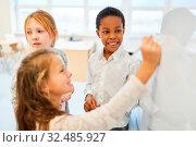 Kinder an der Tafel im Mathematik Unterricht der Grundschule lernen Rechnen. Стоковое фото, фотограф Zoonar.com/Robert Kneschke / age Fotostock / Фотобанк Лори