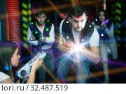 Купить «Emotional guy playing laser tag in colorful beams», фото № 32487519, снято 25 апреля 2018 г. (c) Яков Филимонов / Фотобанк Лори