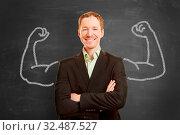 Motivierter Geschäftsmann mit aufgemalten Muskeln vor einer Tafel. Стоковое фото, фотограф Zoonar.com/Robert Kneschke / age Fotostock / Фотобанк Лори