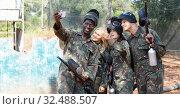 Купить «Cheerful group of paintball players in full gear making selfie with smartphone outdoors», фото № 32488507, снято 11 августа 2018 г. (c) Яков Филимонов / Фотобанк Лори