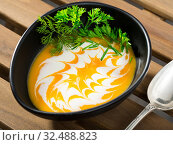Купить «Recipe of pumpkin soup puree with ginger root - roast pumpkin in olive oil, beat in blender with vegetable broth. Add whisked cream with garlic and ginger. Serve with greens», фото № 32488823, снято 3 августа 2020 г. (c) Яков Филимонов / Фотобанк Лори