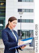 Geschäftsfrau arbeitet mit Stift und Akte vor dem Büro. Стоковое фото, фотограф Zoonar.com/Robert Kneschke / age Fotostock / Фотобанк Лори