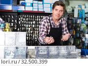 Купить «Worker man in hardware store is trading goods for construction», фото № 32500399, снято 4 мая 2017 г. (c) Яков Филимонов / Фотобанк Лори