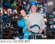 Купить «Young positive couple standing in sports store», фото № 32500407, снято 25 октября 2017 г. (c) Яков Филимонов / Фотобанк Лори